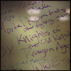 A white board covered in handwritten names of female game characters and the titles of games with women characters like Lisa & Marge from the Simpsons, Knights of the Old Republic, Mortal Kombat, Dragon Age