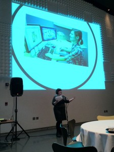 Carly Kocurek speaking at IIT in front of a projected image of a young woman game designer