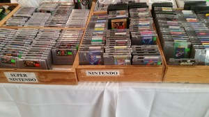 The marketplace at the Midwest Gaming Classic features tables and tables of vintage game cartridges, consoles, and other merchandise.